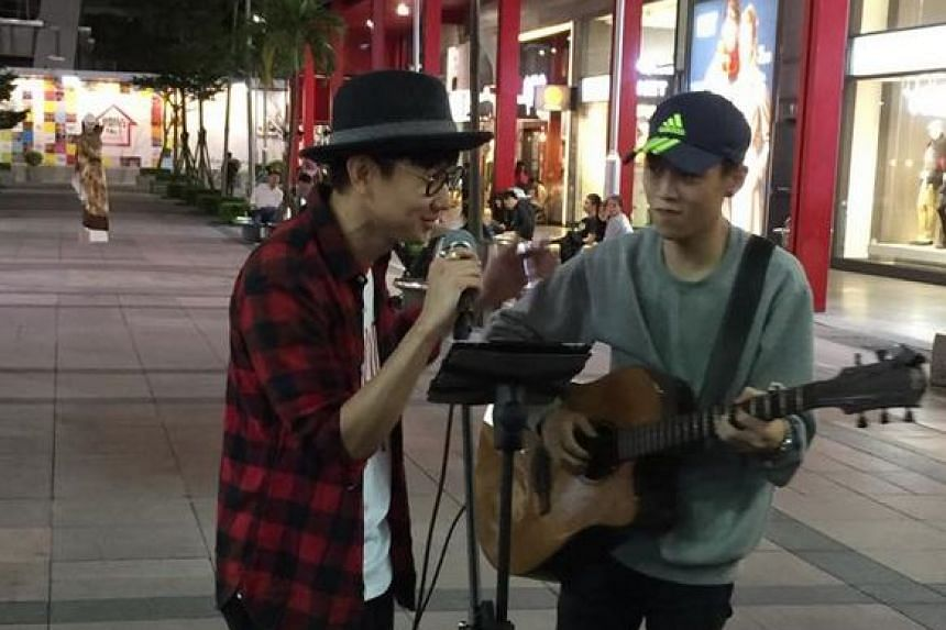 JJ Lin (left) performing the duet with the street busker.