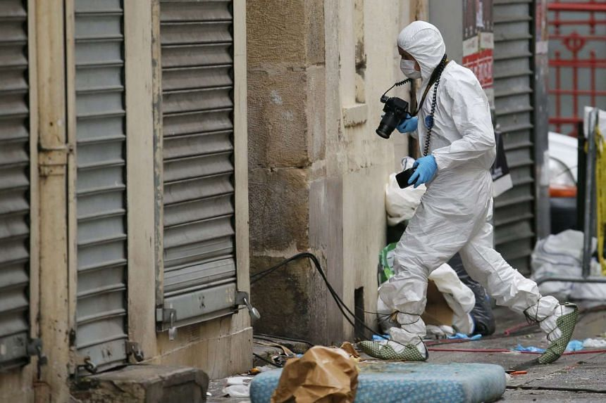 A forensic expert enters a building as he works on the scene in Saint-Denis on Nov 19, 2015.