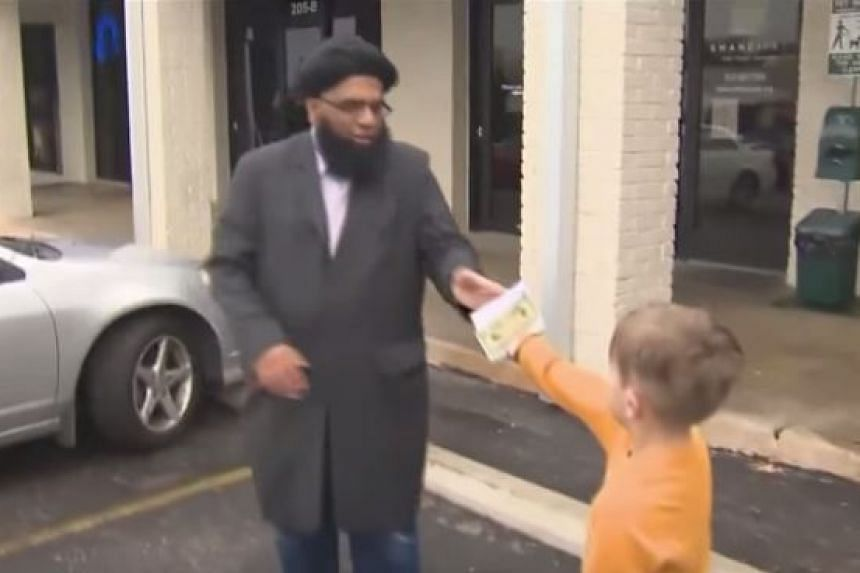Seven-year-old Jack Swanson passing his money to a member of the mosque.