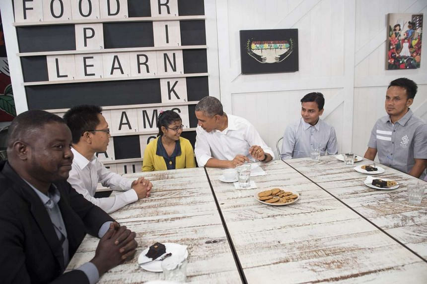 US President Barack Obama (centre) speaking with former refugees who will be moving to the US, following a tour of the Dignity for Children Foundation in Kuala Lumpur on Nov 21, 2015.