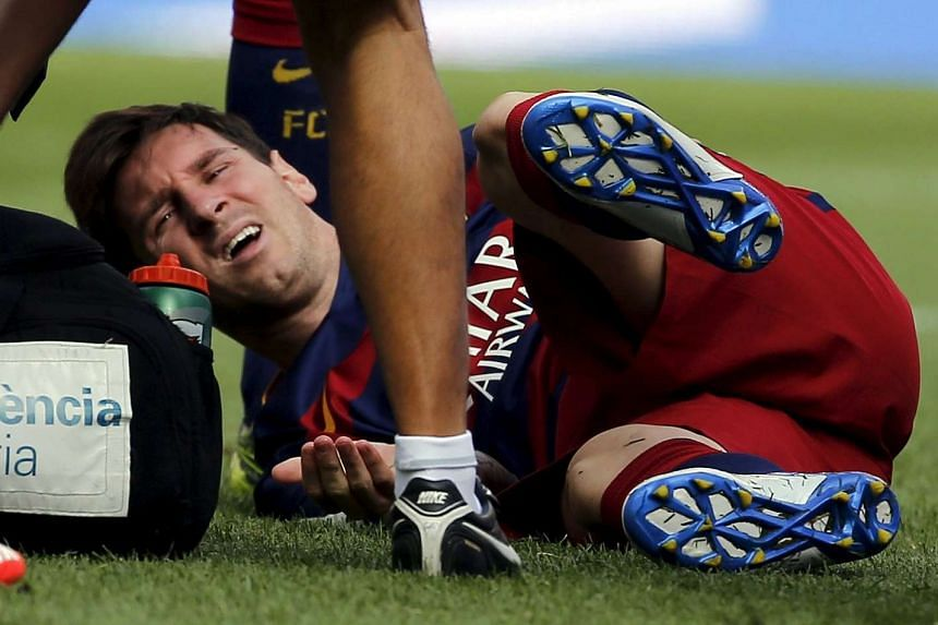 Barcelona's Lionel Messi grimaces as he lies on the pitch after injuring his left knee.