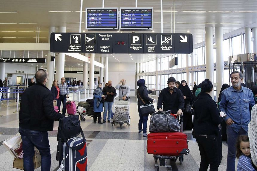 Travellers check flight screens for delays or cancellations at Beirut's Rafik Hariri airport.