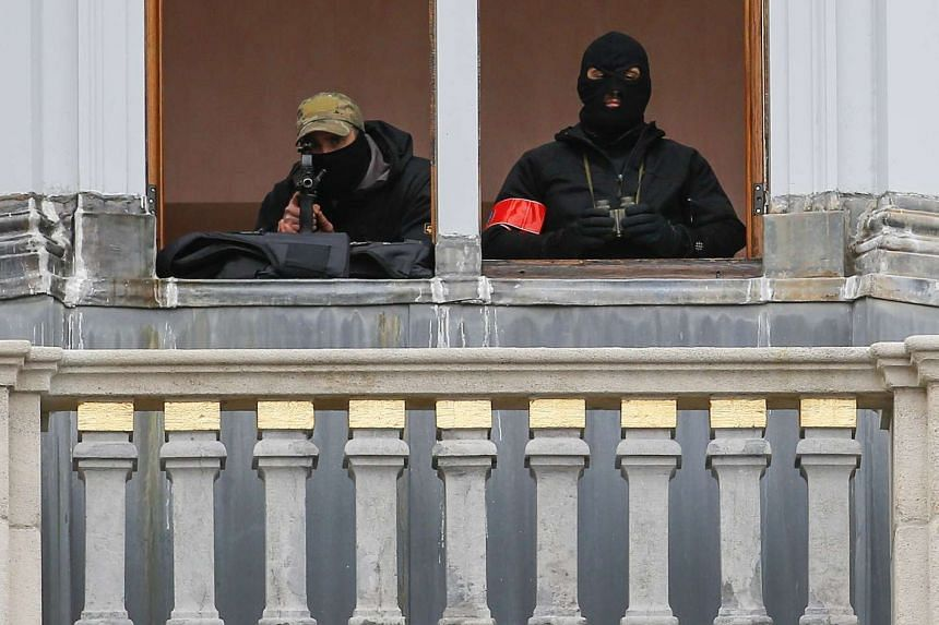 Belgian police special forces are seen on a balcony in Brussels after the country tightened security.