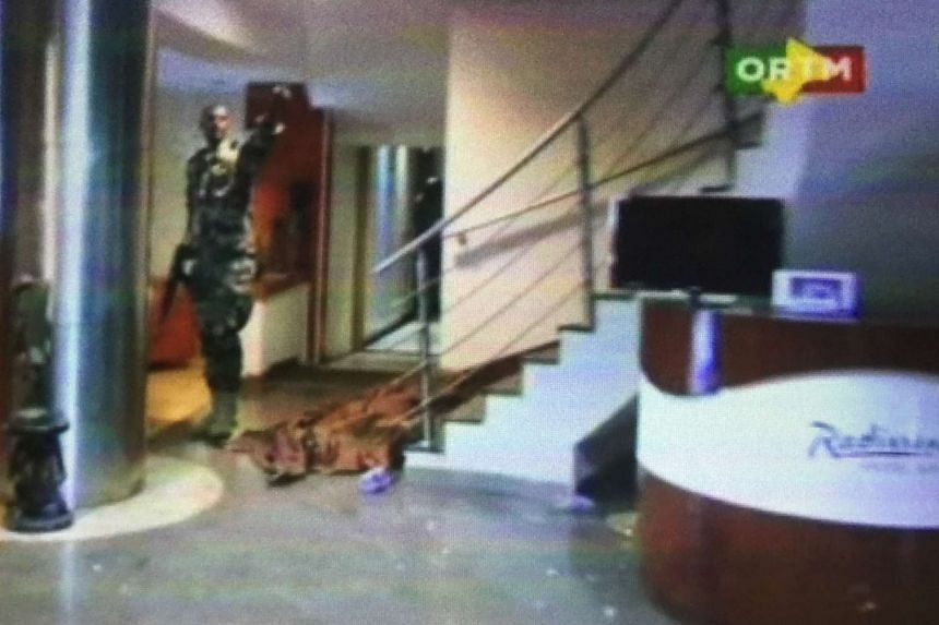 State television broadcast footage of troops in camouflage fatigues wielding AK-47s in the hotel lobby while a body lay under a brown blanket at the bottom of a flight of stairs.