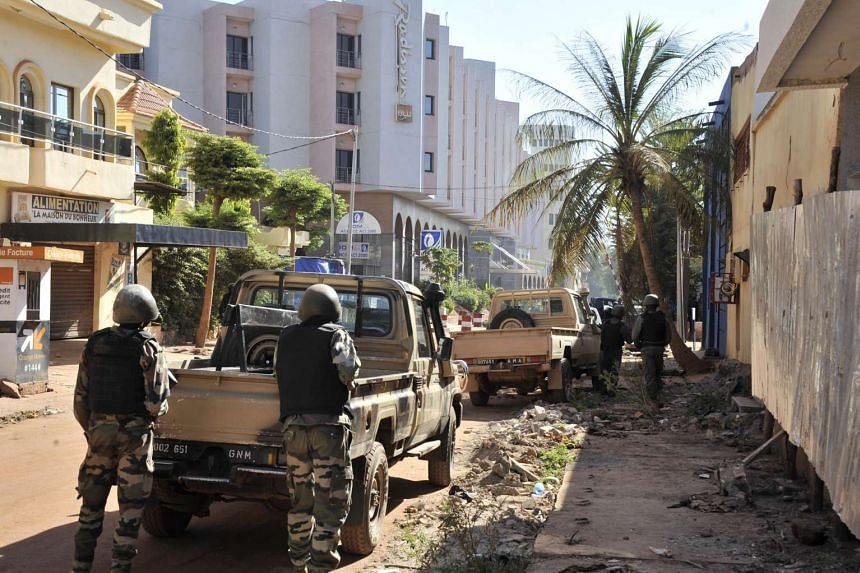 Malian troops taking positions outside the Radisson Blu hotel in Bamako yesterday. According to the operators of the hotel, 125 guests and 13 employees were in the building at their last tally yesterday. US Special Operations forces were helping with