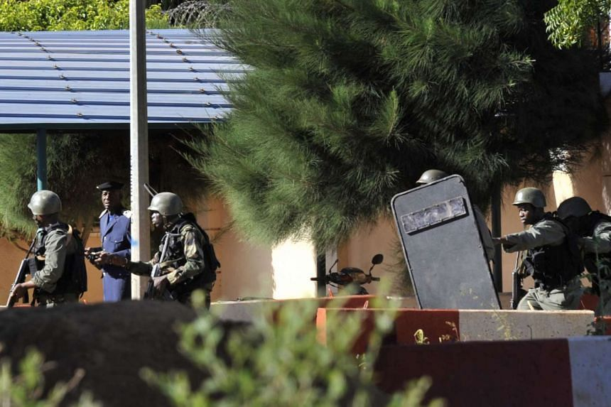 Malian troops taking up positions outside the Radisson Blu hotel in Bamako yesterday. A security source said the gunmen had dug in on the seventh floor of the hotel as special forces advanced on them. Al-Mourabitoun, a group based in northern Mali an