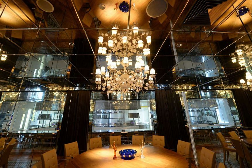 A private dining room (above) has a full view of the chefs at work behind the glass and features a chandelier created out of spoons and teapot parts.