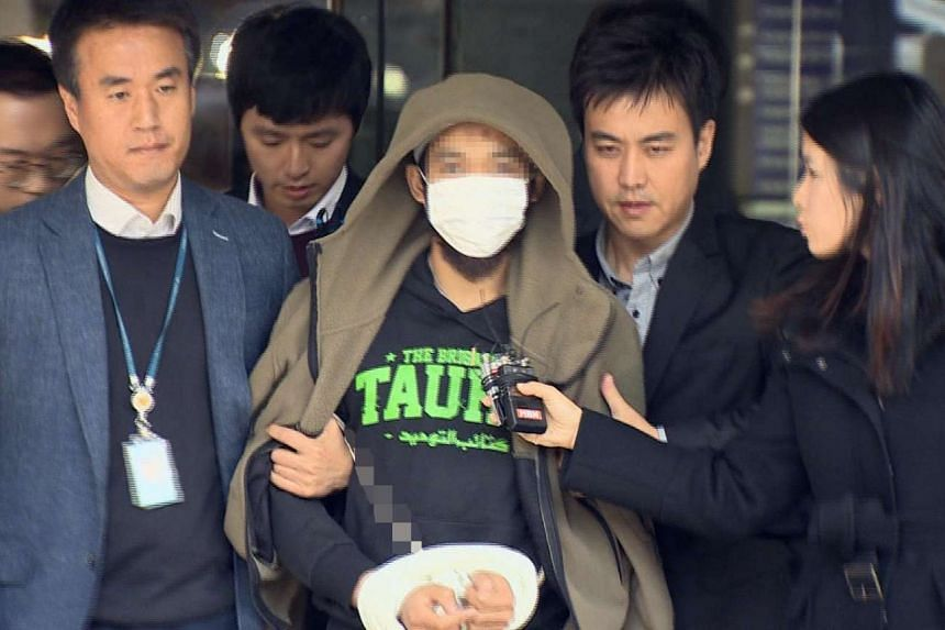 A Yonhap News TV grab shows the Indonesian overstayer leaving a Seoul court yesterday. The terror suspect, 32, was found to have a bowie knife and books on Islamist fundamentalism.