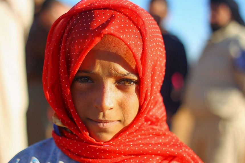 An internally displaced girl stands at a makeshift refugee camp in Sinjar town, in Idlib province, Syria.