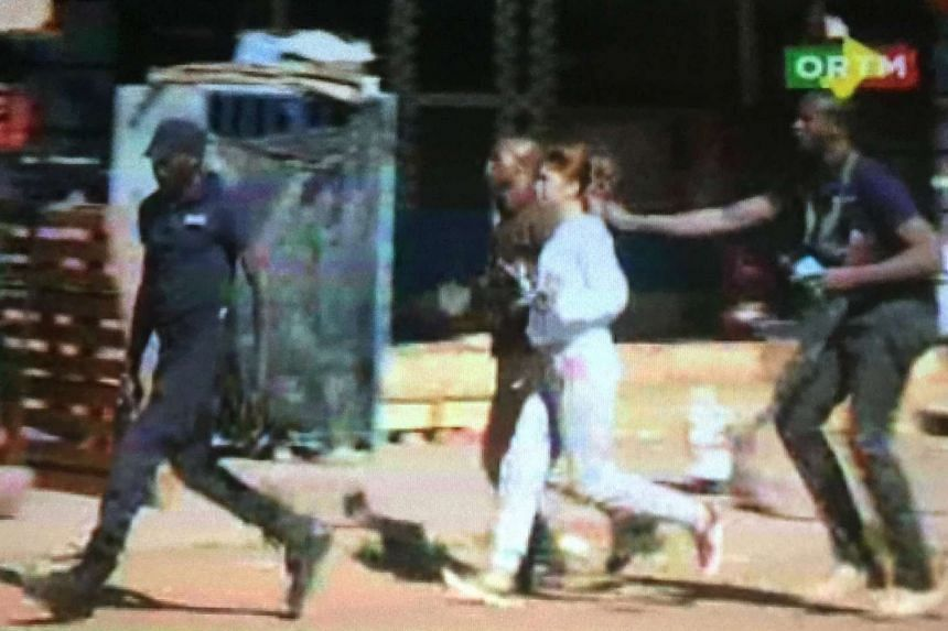 A still image from video shows a hostage rushed out of the Radisson Blu hotel.