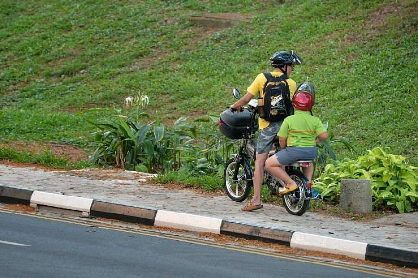A man chatting with his son who was riding pillion on his motorised bicycle on a pavement along Jurong West St 52.