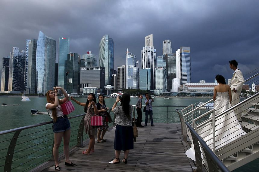 Tourists and a couple take photos along Marina Bay, Mar 9, 2015.