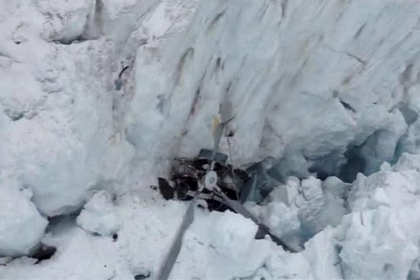 A photograph released by New Zealand police on Nov 21, 2015, shows the remains of the helicopter embedded in the crevasse at Fox Glacier following a crash killing all seven on board.