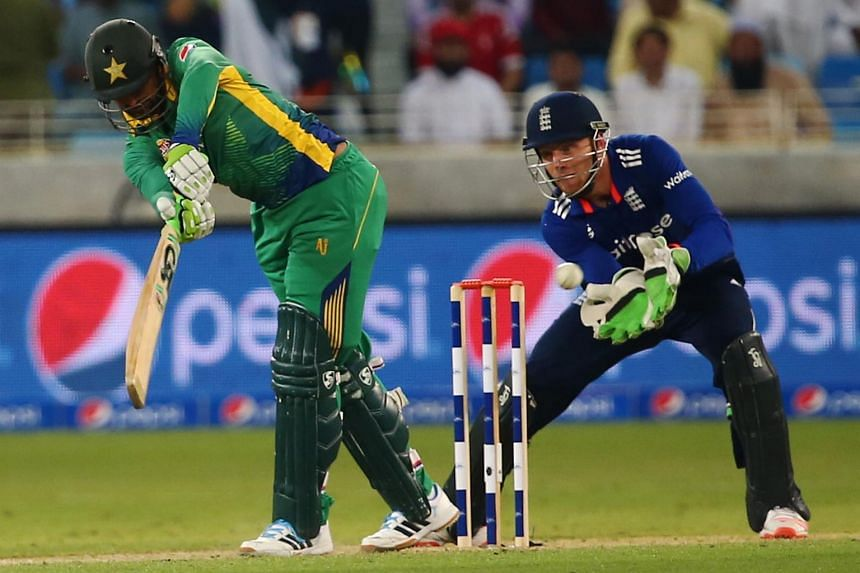 Pakistan's Shoaib Malik (left) plays a shot as England's wicket keeper Jos Buttler reacts during the fourth One Day International Cricket match between Pakistan and England at Dubai Sports City in the Gulf Emirate, on Nov 20, 2015.