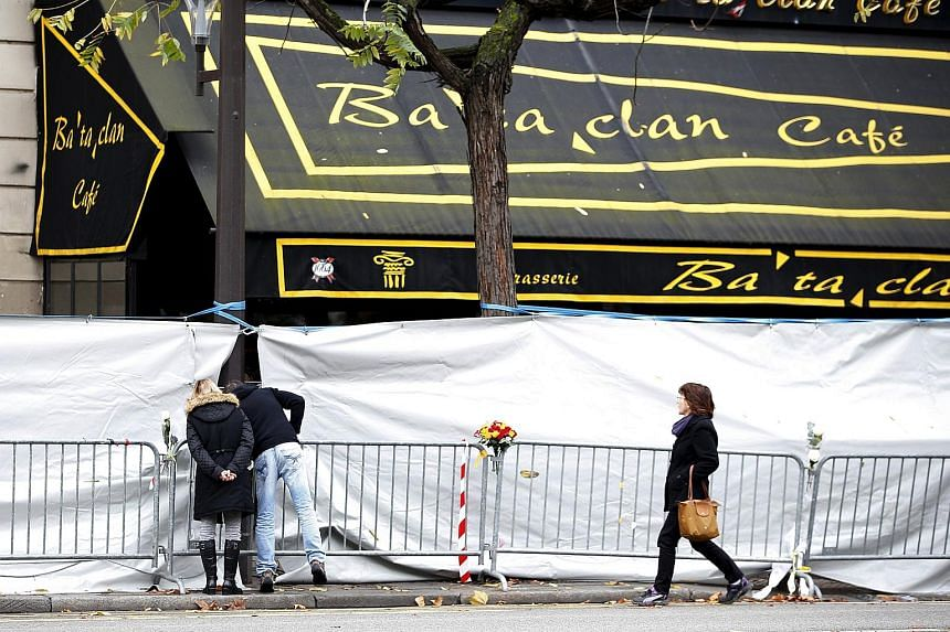 People look through the screened-off facade of the Bataclan Cafe adjoining the concert hall, one of the sites of the deadly attacks in Paris, Nov 21, 2015.
