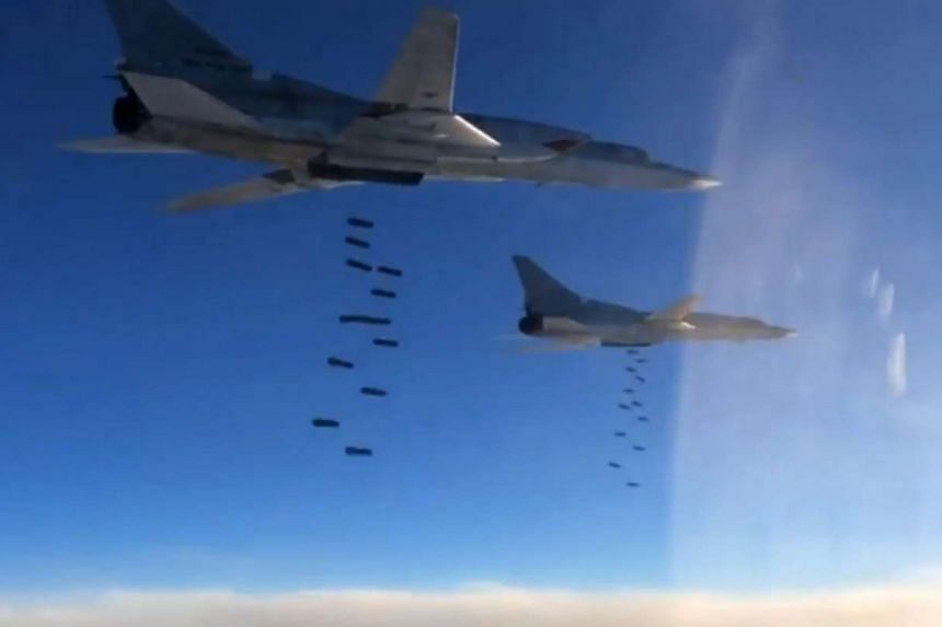 Russian TU-22M3 long-range strategic bombers dropping bombs on targets in Syria, in a screengrab from video footage posted on Nov 18, 2015.