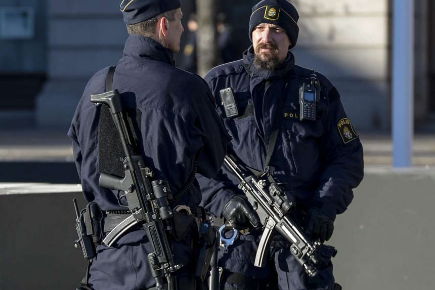 Swedish police standing guard during a rally to honour the victims of the Paris attacks, held at Gustaf Adolf's square in central Stockholm, on Nov 21. 2015.