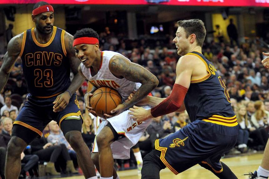Atlanta Hawks Jeff Teague (centre) drives to the basket as Cleveland Cavaliers guard Matthew Dellavedova (right) and LeBron James (left) defend during the game on Saturday (Nov 21).