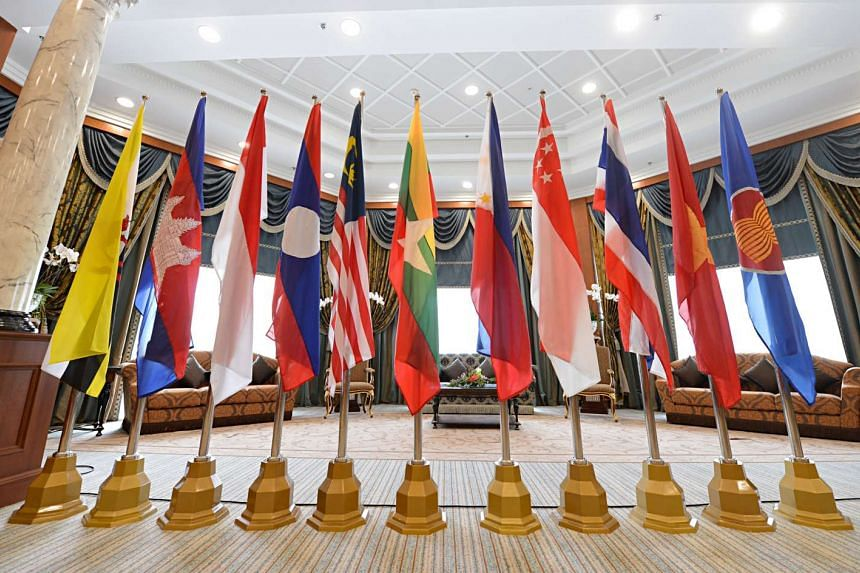 Flags of Asean members are displayed in a conference room.
