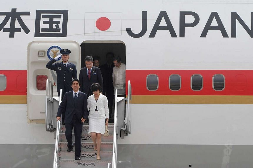 Japan's Prime Minister Shinzo Abe (left) and his wife Akie arrive to take part in the Asia-Pacific Economic Cooperation (APEC) Summit in Manila.