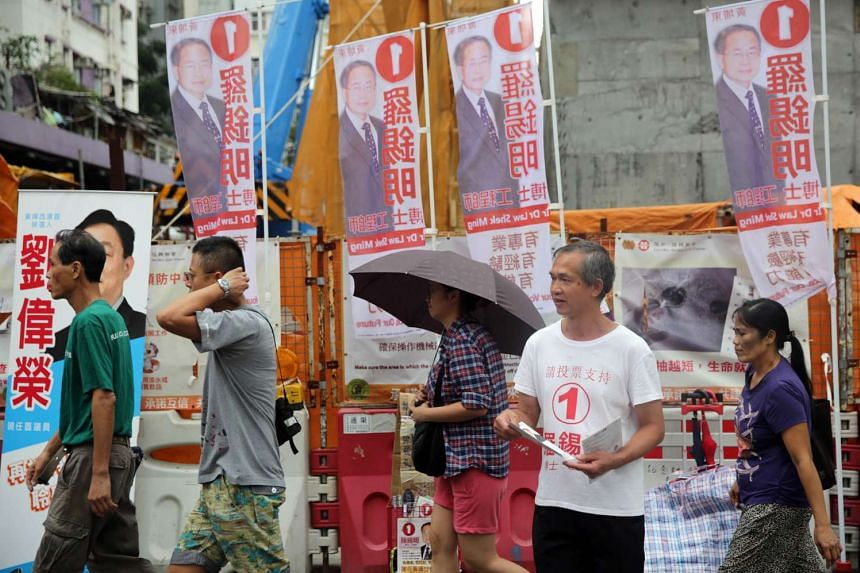 A volunteer (2nd from right) hands out campaign information for independent candidate Law Shek Ming (not pictured) in the Whampoa District of Hong Kong on Nov 16, 2015 in the lead up to local elections.