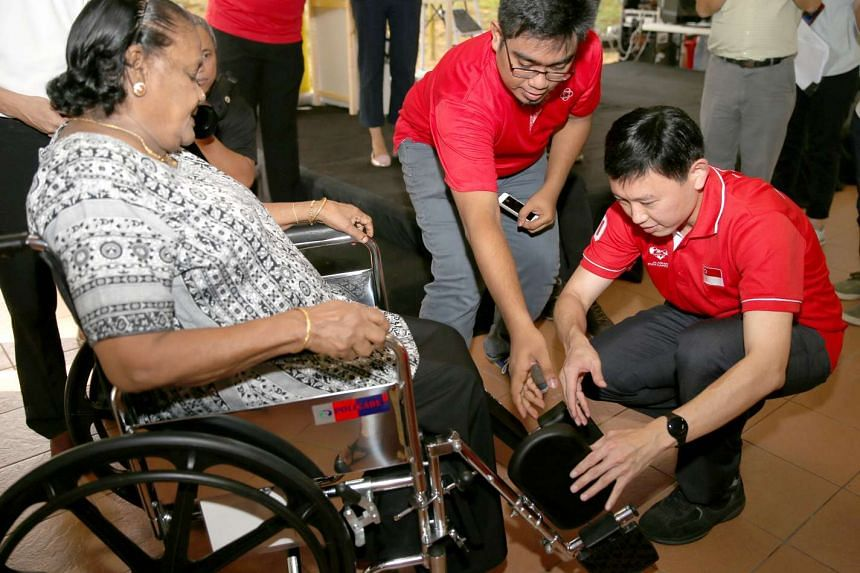 Bishan-Toa Payoh MP Chee Hong Tat helping Toa Payoh resident Madam Paruvadi Duraisamy, 84, into a borrowed wheelchair at the launch of Resource Centre @ RC on Nov 21, 2015.
