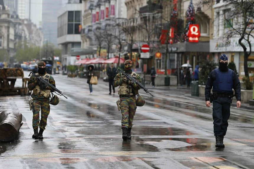 Belgian soldiers and a police officer patrolling central Brussels on Nov 21, 2015, after security was tightened in Belgium following the fatal attacks in Paris.