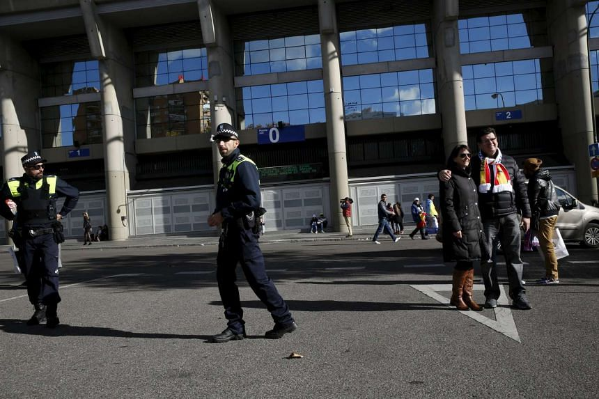 Police officers stand guard next to soccer fans having their picture taken outside the Santiago Bernabeu stadium before the 'Clasico' soccer match between Real Madrid and Barcelona in Madrid, Spain, on Nov 21, 2015.