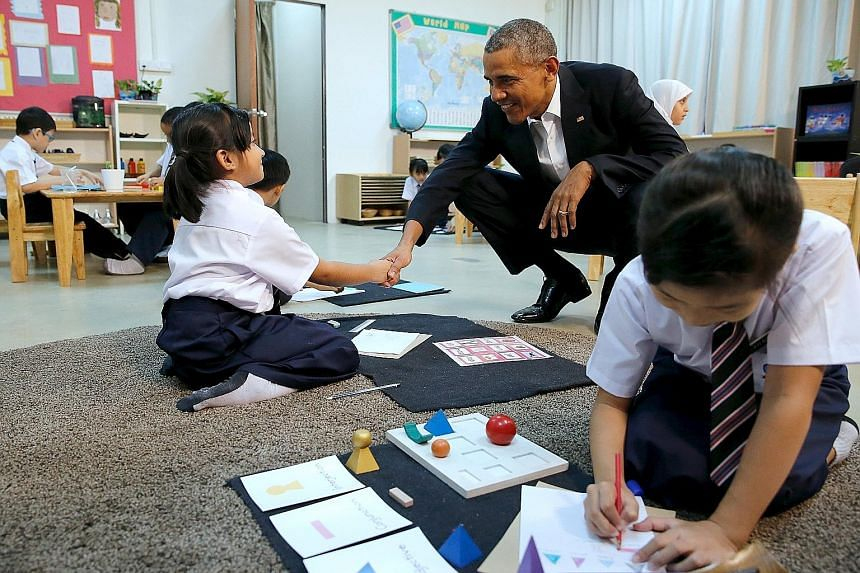 US President Barack Obama receiving a hug from a refugee (left) and greeting a student (right) while touring the Dignity for Children Foundation - which runs classes for poor children, including refugees - in Kuala Lumpur yesterday. Mr Obama has vowe