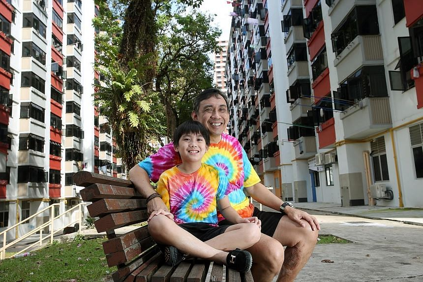 Mr Raymond Khoo and his son Justin. The eight-year-old boy helps his father distribute food to residents from six blocks of one-room rental units in Lengkok Bahru, one of Singapore's poorest neighbourhoods.