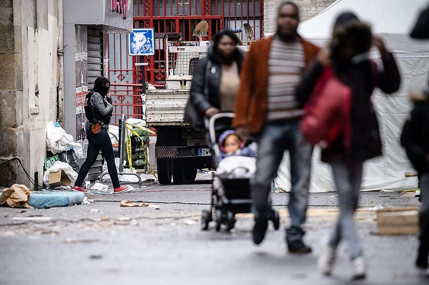 Residents walking near a rue du Corbillon building in Saint Denis, a northern Paris suburb, on Thursday. French police launched a raid in the suburb early on Wednesday in connection with the Nov 13 terrorist attacks.