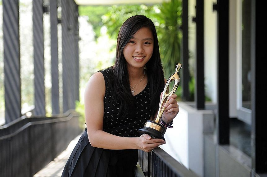 National badminton player Yeo Jia Min posing with The Straits Times' Star of the Month award for October. Her title wins (both singles and doubles) at the Badminton Asia Under-17 tournament won her the accolade.