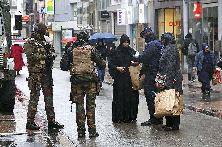 Belgian soldiers patrolling the streets while a police officer checks the documents of a woman shopping in central Brussels yesterday. Belgium raised the alert status for its capital to the highest level yesterday, shutting the metro and warning the