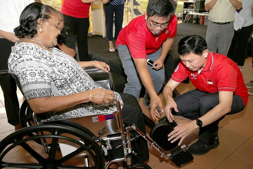Mr Chee Hong Tat (right), an MP for Bishan-Toa Payoh GRC, helping Toa Payoh resident Paruvadi Duraisamy, 84, with her borrowed wheelchair.