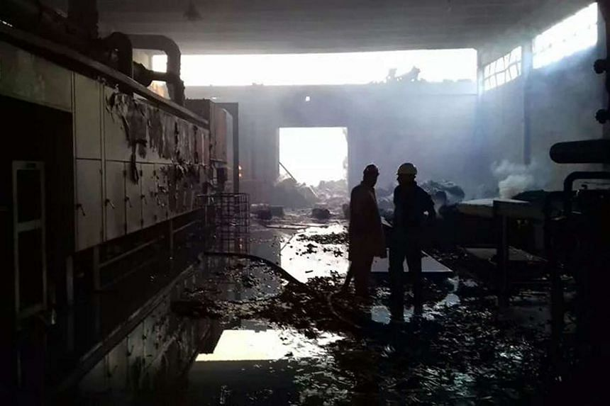 Pakistani firefighters stand in a burnt-out factory torched by an angry mob in Jehlum.