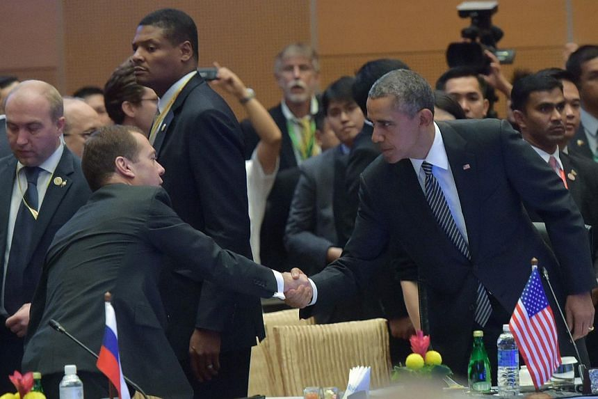 Russian Prime Minister Dmitry Medvedev (left) shakes hands with Barack Obama before a session of the 10th East Asia Summit.