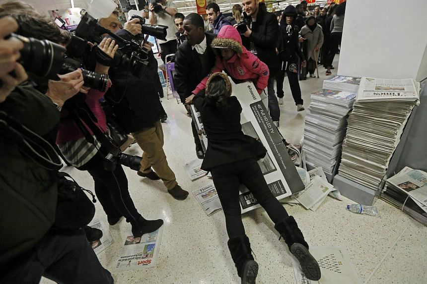 Shoppers wrestle over a television as they compete to purchase retail items on Black Friday.