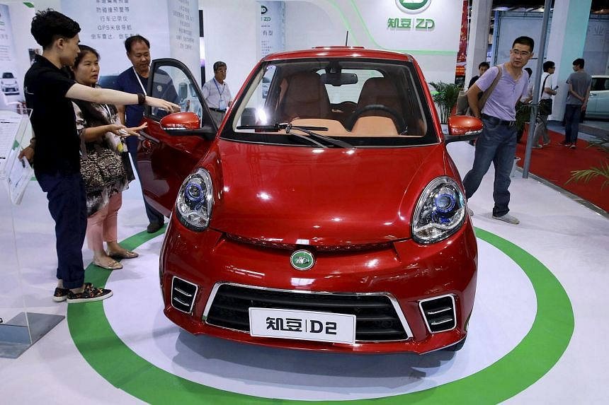 Visitors look at an electric car on display at the 11th Beijing International Pure Electric Vehicles, Hybrid Electric Vehicles and Charging Ctation Exhibition in Beijing.