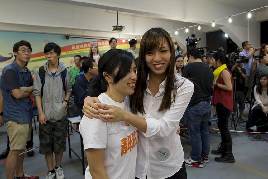 Kwong Po Yin (left), member of Umbrella soldier group, Youngspiration, is hugged by her election partner, Yau Wai Ching after winning a district council election.