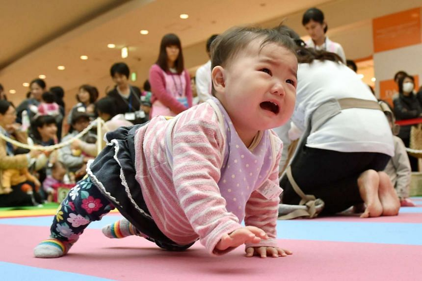 A baby competes in a baby crawling competition hosted by a Japanese magazine in Yokohama, Kanagawa prefecture on Nov 23, 2015.