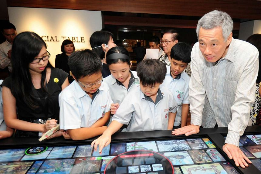 Singapore Prime Minister Lee Hsien Loong (right) and school children look at digital interactive media during the opening of the newly restored National Gallery on Nov 23, 2015.