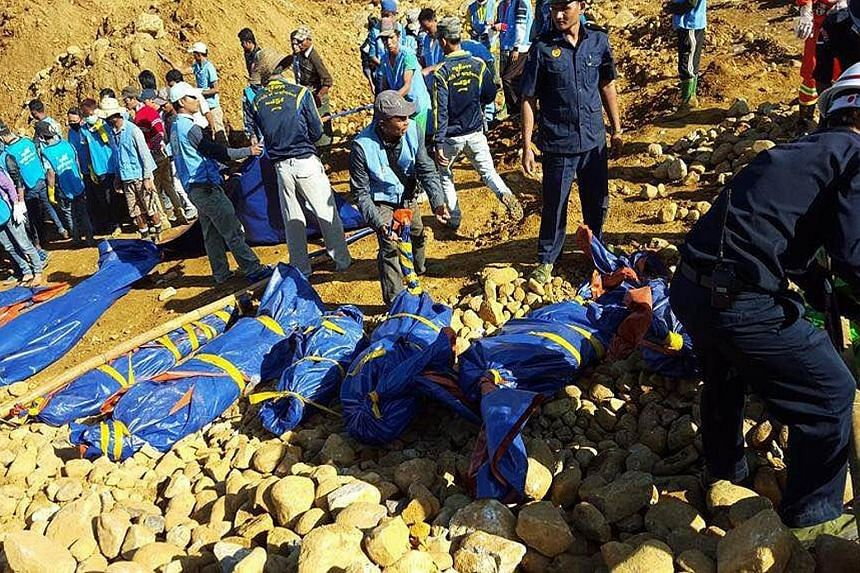 Rescue workers collecting bodies of people killed in the landslide on Saturday in the jade-mining area of Hpakant, in Myanmar's Kachin state. Hpakant produces some of the world's highest-quality jade but its mines and dump sites for debris are rife w