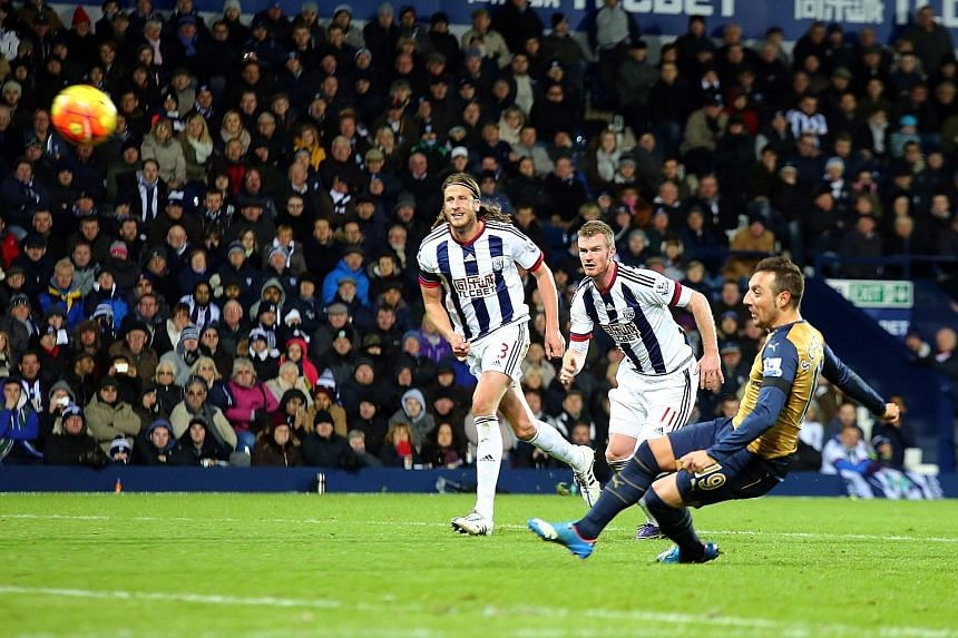 Arsenal's Spanish midfielder Santi Cazorla (right) slipping as he sends his miscued penalty over the bar to compound the Gunners' woes.