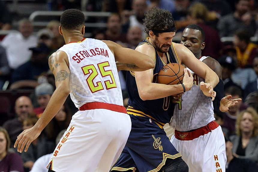 Cleveland Cavaliers forward Kevin Love driving through Atlanta Hawks guard Thabo Sefolosha and forward Paul Millsap during the third quarter at Quicken Loans Arena. He scored scored 25 points and grabbed 11 rebounds as the Cavs won 109-97. LeBron Jam