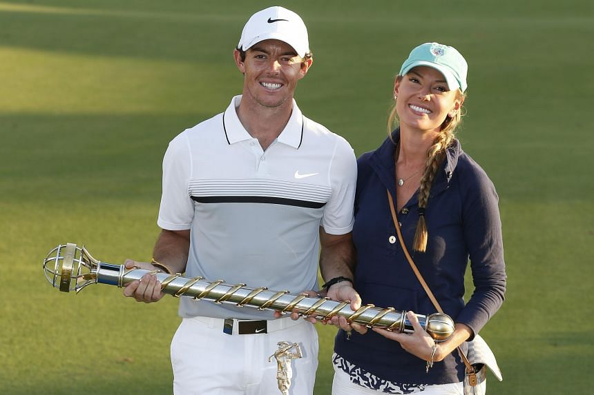 Northern Ireland's Rory McIlroy with his girlfriend Erica Stoll and his trophies after winning the DP World Tour Championship in Dubai to finish the season as Europe's top golfer and retain his Race to Dubai title.
