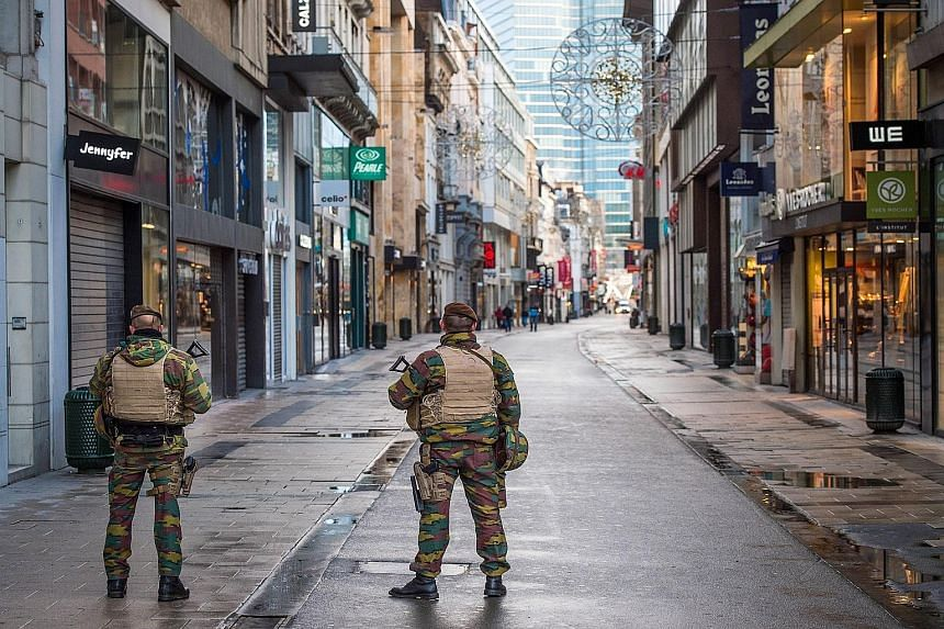 """Belgian soldiers on patrol in Rue Neuve, usually the busiest shopping street in Brussels but empty yesterday after the terror alert was raised to the highest level of four because of what officials said was an """"imminent threat""""."""