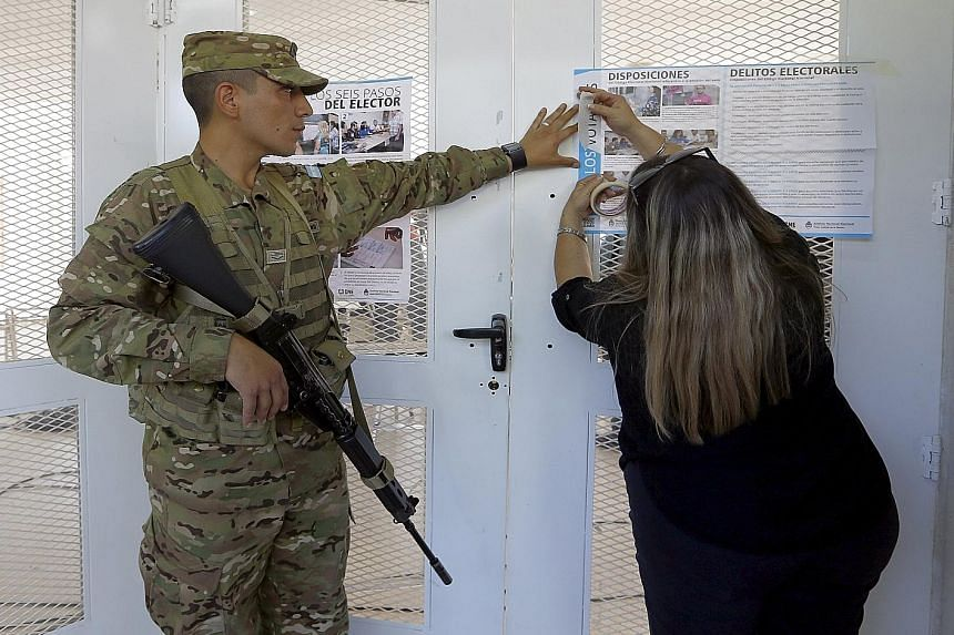 An electoral officer putting up a sheet of rules for voting at a polling station in Buenos Aires. This election has been unique, with the first national run-off vote and the first televised candidate debate.