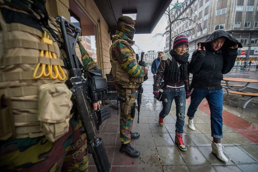Armed military men stand guard in front of a restaurant in downtown Brussels, Belgium.