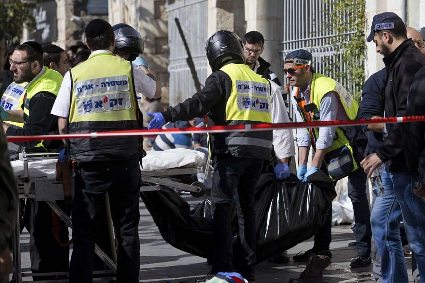Voluneers evacuate the body of a Palestinian girl where two girls stabbed passers-by in Jerusalem  on Monday.