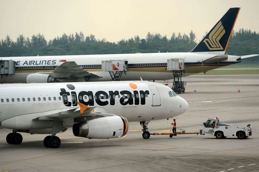 A Tigerair plane (foreground) and a Singapore Airlines plane at Changi Airport.